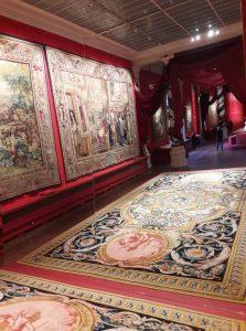 Miroir penché reflétant un tapis de la Savonnerie et des pièces de la tenture de l'Histoire du Roi.