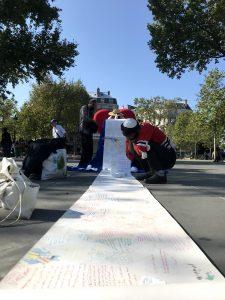 """Un SDF accroupi en train de lire """"The World Letter"""" - Dimanche 13 sept, Place de la République."""